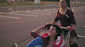 Arbeiten Sie lustigem jungem Hippie die jugendlich Mädchen um, die Spaß am Einkaufszentrumparken haben, Reiten im Warenkorb halte stock video footage