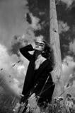 Arbeiten Sie Mädchen im schwarzen Mantel um, der im Gras nahe einem hölzernen Pfosten steht Stockfotografie