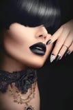 Arbeiten Sie Mädchen mit schwarzer gotischer Frisur, Make-up, Maniküre und Zubehör um Stockfotografie
