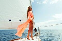 Arbeiten Sie Mädchensegelsport im Meer mit Sonnenlicht des blauen Himmels um Stockbild