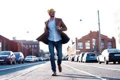 Arbeiten Sie Mannportrait um Junger Mann in den Gl?sern, die Mantel gehend hinunter die Stra?e tragen stockbilder