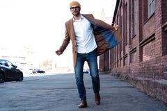 Arbeiten Sie Mannportrait um Junger Mann in den Gl?sern, die Mantel gehend hinunter die Stra?e tragen lizenzfreie stockbilder