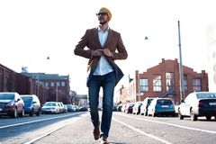 Arbeiten Sie Mannportrait um Junger Mann in den Gl?sern, die Mantel gehend hinunter die Stra?e tragen lizenzfreie stockfotografie