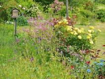 Arbeiten Sie mit bunten Blumen und einem Vogelkasten Frankreich im Garten Stockbild