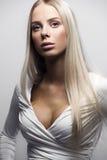Arbeiten Sie Porträt überzeugten Blondine im weißen Kleid um Stockfoto