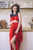 Arbeiten Sie Porträt attraktiver stilvoller schwangerer Dame in langem rotem sarafan und des Strohhutes um, Foto vom glücklichen  stockbild