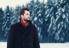 Arbeiten Sie Porträt den hübschen eleganten bärtigen Mann um, der schwarzen Mantel am Wintertag über schneebedecktem Baumwaldhint Stockfoto