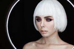 Arbeiten Sie Porträt der jungen Schönheit mit dem ausgezeichneten blonden Haar um, das auf schwarzem Hintergrund lokalisiert wird Lizenzfreies Stockfoto