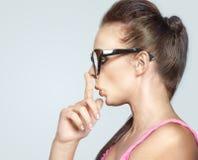 Arbeiten Sie Porträt der lustigen Frau durch die Fingerspitze um, die ihre Nase berührt Stockfoto