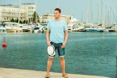 Arbeiten Sie Porträt des gutaussehenden Mannes auf Pier gegen Yachten um Stockbilder