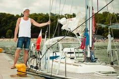 Arbeiten Sie Porträt des gutaussehenden Mannes auf Pier gegen Yachten um Lizenzfreies Stockfoto