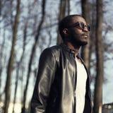 Arbeiten Sie Porträt des hübschen afrikanischen Mannes in der schwarzen Lederjacke um Stockfotografie