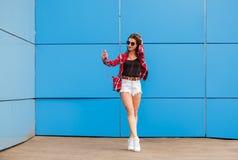 Arbeiten Sie Porträt des hübschen lächelnden Hippie-Mädchens in der Sonnenbrille mit dem Smartphone und Kopfhörern um, die selfie Stockbild