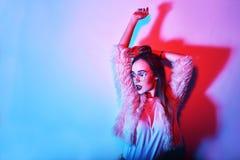 Arbeiten Sie Porträt des jungen eleganten Mädchens in den Gläsern um Farbiger Hintergrund, Atelieraufnahme Schöne Brunette-Frau H stockfotografie