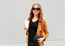 Arbeiten Sie Porträt die hübsche lächelnde Frau mit Kaffeetasse und Handtaschenkupplung gehend über Grau um Stockbild