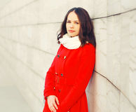 Arbeiten Sie Porträt die schöne junge Frau um, die einen roten Manteljackenschal in der Stadt trägt stockfotografie