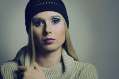 Arbeiten Sie Porträt einer blonden Frau um, die einen Rollkragen und einen Hut trägt Stockfoto