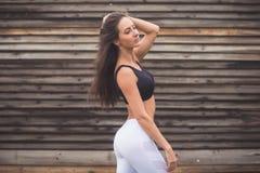 Arbeiten Sie Porträt eines jungen athletischen Sitzmädchens in der Sportkleidung draußen um Frau mit perfektem Körper Eignungskon lizenzfreie stockbilder
