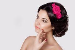Arbeiten Sie Porträt eines schönen sexy netten Brunette mit schönem stilvollem Haarschnitt, hellem Make-up und Blumen in ihrem Ha Stockfoto