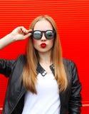 Arbeiten Sie Porträt hübsche Blondine mit dem roten Lippenstift um, der eine Felsenschwarzart und -Sonnenbrille haben Spaß trägt Stockbild