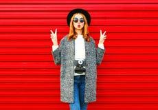 Arbeiten Sie Porträt hübsche Frau mit der Retro- Kamera um, die auf einem Rot aufwirft stockbild