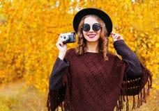 Arbeiten Sie Porträt hübsche lächelnde Frau mit tragender Sonnenbrille des schwarzen Hutes des Herbstes der Retro- Kamera und ges Stockfotografie