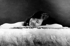 Arbeiten Sie Porträt im Studio der schönen jungen Frau um, die mit ihrer Flöte gegen dunklen Hintergrund im Studio glücklich sich stockfotografie