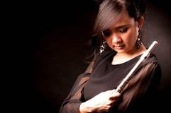 Arbeiten Sie Porträt im Studio der schönen jungen Frau um, die mit ihrer Flöte gegen dunklen Hintergrund im Studio glücklich sich stockfoto