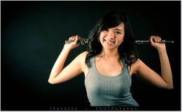 Arbeiten Sie Porträt im Studio der schönen jungen Frau um, die mit ihrer Flöte gegen dunklen Hintergrund im Studio glücklich sich lizenzfreie stockfotografie