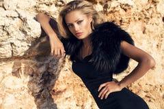 Arbeiten Sie Porträt ob schönes Mädchen mit dem blonden Haar im eleganten Kleid und im Pelz um Stockfotografie