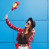 Arbeiten Sie Porträt von recht lächeln und Frau in der Sonnenbrille über der bunten blauen Wand um Ballon in ihrer Hand outdoor Stockfotografie