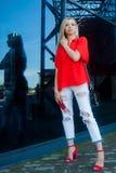 Arbeiten Sie Porträt von recht lächeln und Frau im roten Hemd mit Smartphone nahe Einkaufszentrum um Lizenzfreies Stockbild
