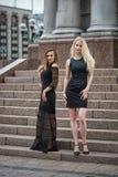 Arbeiten Sie Porträt von zwei stilvollen hübschen Frauen um, die auf der Straße am regnerischen Tag aufwerfen Lizenzfreies Stockbild