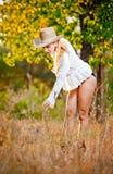 Arbeiten Sie Porträtfrau mit Hut und weißem Hemd am Herbsttag um Stockfoto