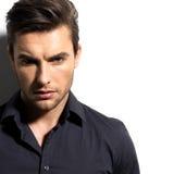 Arbeiten Sie Porträt des jungen Mannes im schwarzen Hemd um Stockbild