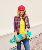 Arbeiten Sie Porträt des recht kühlen Mädchens in der roten Kappe um Stockfotografie