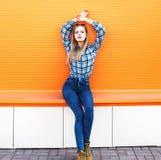 Arbeiten Sie recht blondes Mädchenmodell über bunter Orange um Lizenzfreie Stockfotos