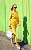 Arbeiten Sie recht junge Frau in der gelben Klagenkleidung mit Handtasche um Stockfotografie