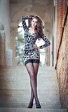 Arbeiten Sie recht junge Frau mit der langen Beinaufstellung um, die auf der Treppe nahe einer alten Steinwand im Freien ist. Schö Lizenzfreies Stockfoto