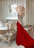 Arbeiten Sie schönes blondes Mädchenmodell mit eleganter Frisur im Rot um Stockfoto