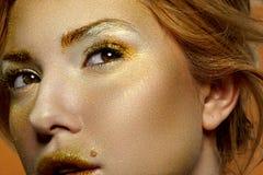 Arbeiten Sie Schönheit weibliches blondes Modell mit Goldgesicht um Stockfotos