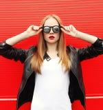 Arbeiten Sie stilvolle Frau des Porträts recht mit dem roten Lippenstift um, der eine Felsenschwarzjacke und -Sonnenbrille trägt Stockfotos