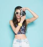Arbeiten Sie stilvolles Frauentanzen und Herstellungsfoto unter Verwendung der Retro- Kamera um Porträt auf blauem Hintergrund in Stockbild
