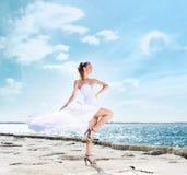 Arbeiten Sie Trieb einer jungen Frau auf einem Seehintergrund um Stockfotografie