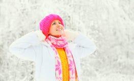 Arbeiten Sie Winterporträt die glückliche Frau um, die einen bunten Strickmützestrickjackenschal über schneebedecktem Hintergrund stockfotografie