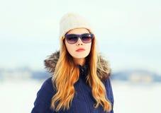 Arbeiten Sie Winterporträt hübsche Blondine tragende Sonnenbrille eines Jackenhutes um Stockfotografie