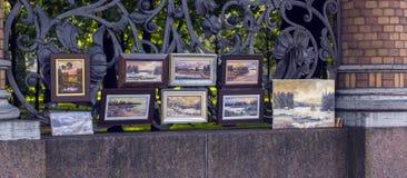 Arbeiten von Künstlern im Verkauf in der Straße auf dem Zaun des Mikhailovsky-Gartens Stockfotografie