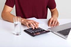 Arbeitendes Prozesskonzept Geschäftsmann in der kastanienbraunen Ausstattung, die am weißen Tisch mit neuem Finanzprojekt im Büro stockfotos