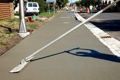 Arbeiter beendet und macht Betondecke auf neuem Bürgersteig glatt stockfotos