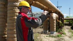 Arbeiter an den Energiegerätelistevideos auf seinem Smartphone stock footage